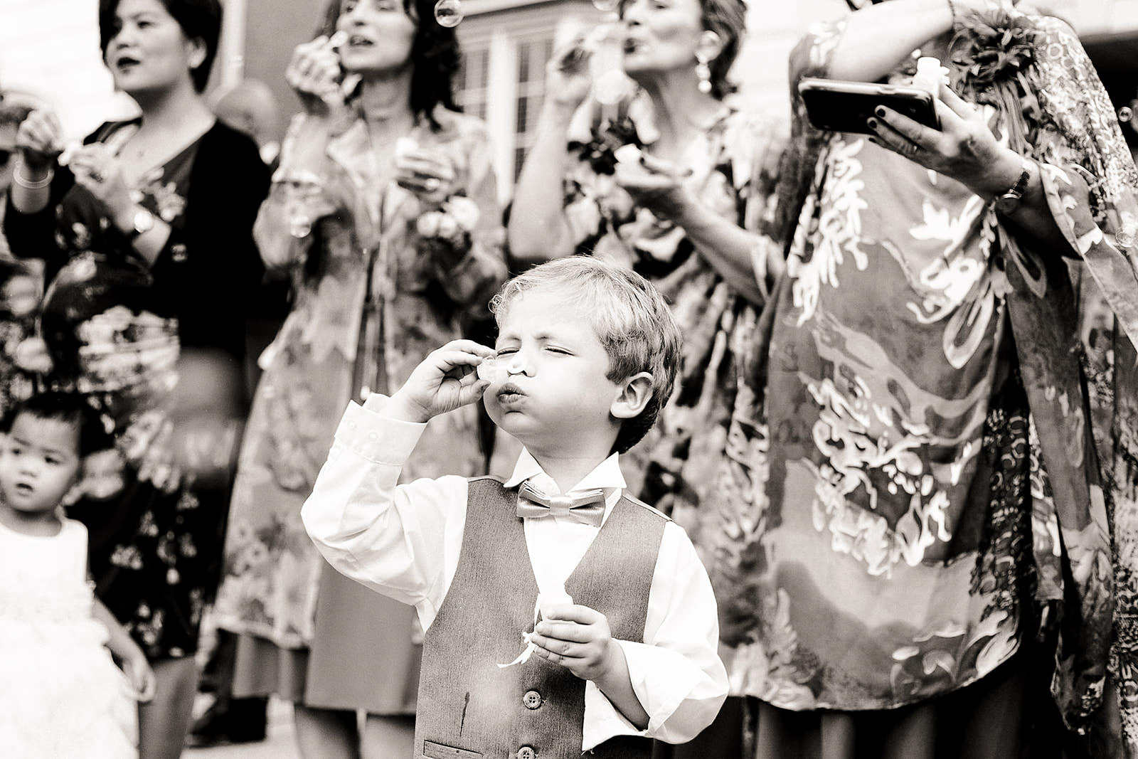 Cute little boy blowing bubbles at wedding